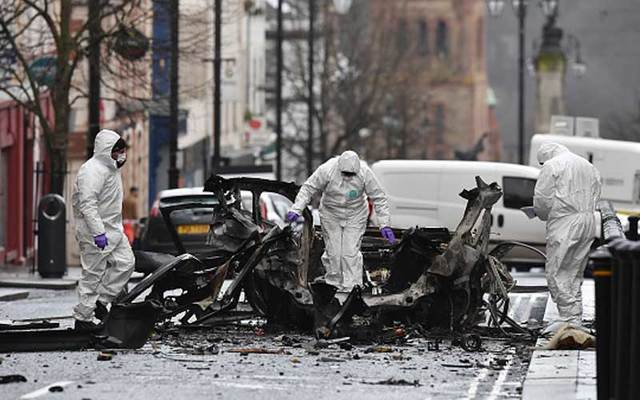 Forensic officer inspect the remains of the vehicle used as a car bomb outside the court house in Derry on Saturday, January 20.