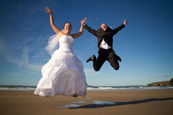 Happy Irish wedding couple celebrating on a beach.