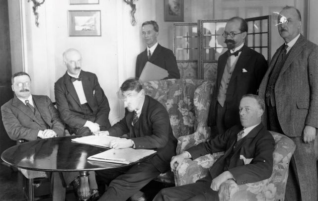 The signing of the Irish Free State Treaty in London, December 6, 1921. From left: Arthur Griffith, Eamon Duggan, Michael Collins, Robert Barton. Standing from left: Robert Erskine Childers, George Gavan Dufy, and John Chartres
