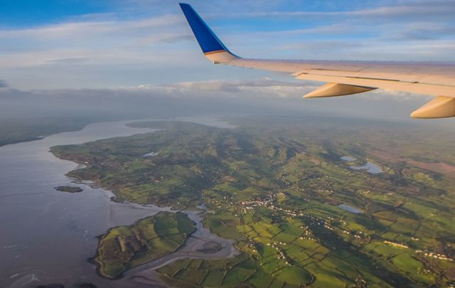An airplane wing and a view from above of wild and impossibly green Ireland.