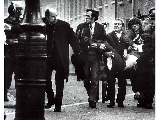 An iconic shot from Bloody Sunday of a wounded man being carried from the street by civil rights marchers.
