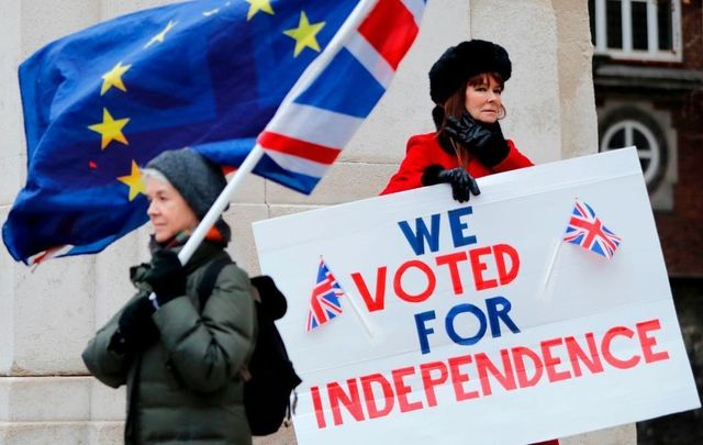 A pro-Brexit activist (R) holds a placard reading \'We Voted For Independence\' as an anti-Brexit campaigner waves a European Union and a Union flag.
