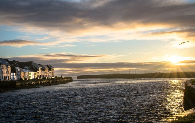 A picture of Galway Harbor in Ireland at sunrise.\n