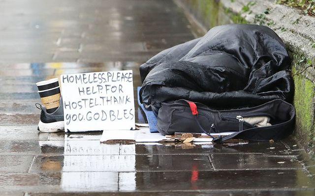 A beggar sits next to an ATM in Dublin.