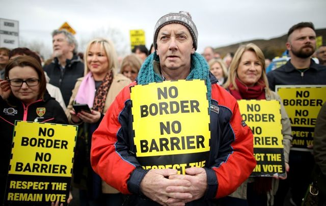 Protesters against any border between Ireland and Northern Ireland because of Brexit hold placards at the Carrickcarnan border between Newry in Norther Ireland and Dundalk in the Irish Republic on March 30, 2019.