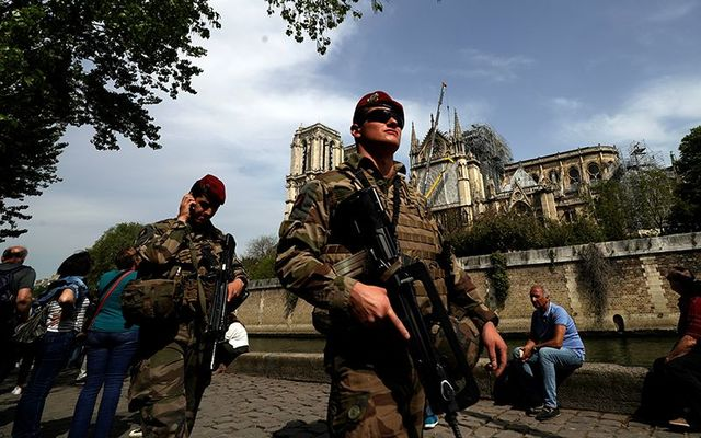 Military patrol Notre Dame cathedral after the fire.