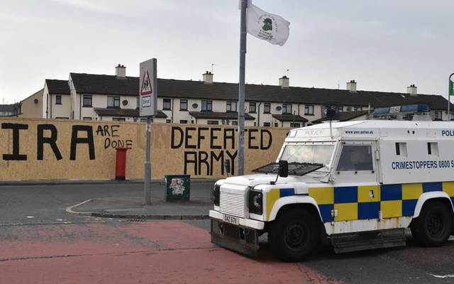 Police van parked near graffiti which says \'IRA are done\' and \'Defeated Army\' in Derry, Northern Ireland.