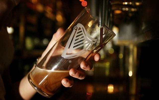 Why do bubbles in a pint of Guinness go down rather than up?