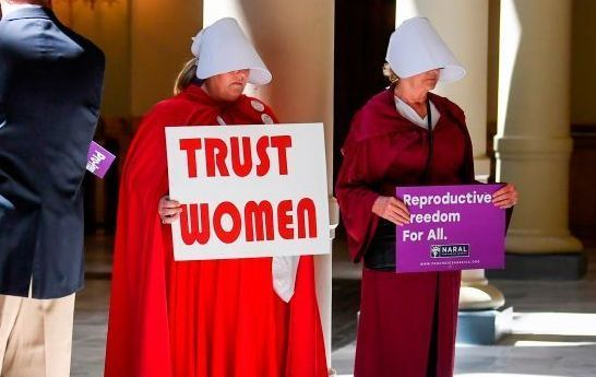 "Activist Tamara Stevens (L) with the Handmaids Coalition of Georgia holds a sign as Democratic presidential candidate Sen. Kirsten Gillibrand (D-NY) addresses an event at the Georgia State Capitol to speak out against the recently passed ""heartbeat\"" bill on May 16, 2019, in Atlanta, Georgia."