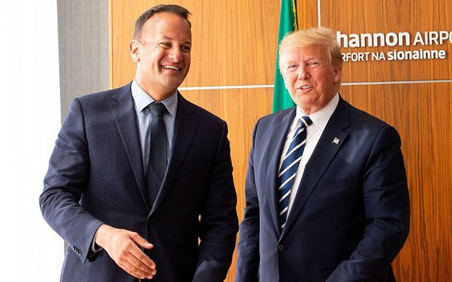 US President Donald Trump signs the visitors\' book as Taoiseach Leo Varadkar (L) and First Lady Melania Trump (R) watch on at Shannon Airport on June 5, 2019, in Shannon, Ireland.