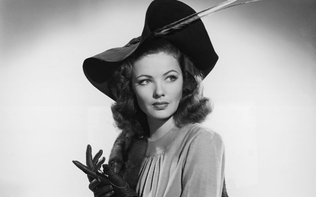 Studio portrait of American actor Gene Tierney (1920 - 1991) seated on a divan. She is wearing a hat with a feather, a mink stole, and leather gloves.