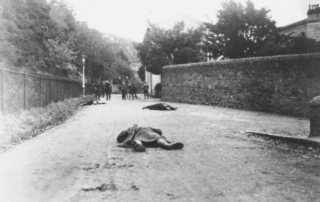 The bodies of dead Sinn Féin supporters lie in the foreground, and in the background, a group of men is arrested by the Royal Irish Constabulary, Ireland, November 1920.