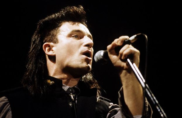 Bono performing live onstage on The Unforgettable Fire tour, at \'The Longest Day\' concert.