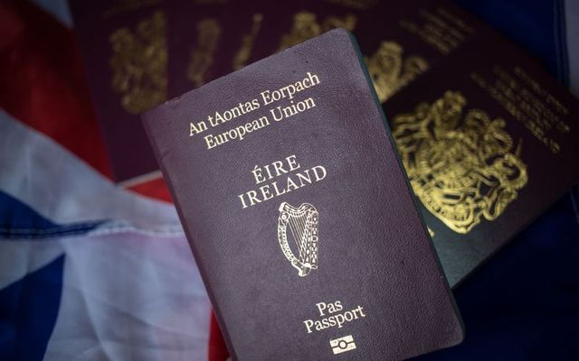 An Irish passport is held over UK passports.