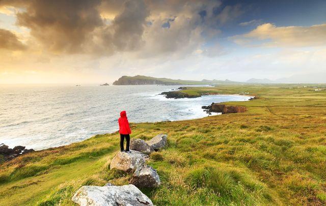 A woman exploring the coastline near Sybil head along the Dingle peninsula.