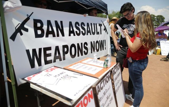 A \'Ban Assault Weapons Now\' sign is displayed near a voter registration table at a protest against President Trump\'s visit, following a mass shooting which left at least 22 people dead, on August 7, 2019, in El Paso, Texas.