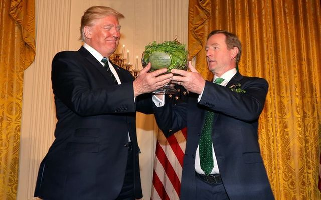 Donald Trump receiving a bowl of shamrock from Enda Kennedy on St. Patrick\'s Day in 2017.