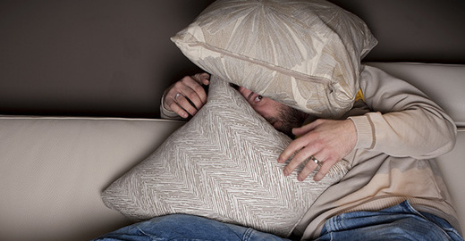 Cropped_cut_man_couch_watching_scary_movie_istock