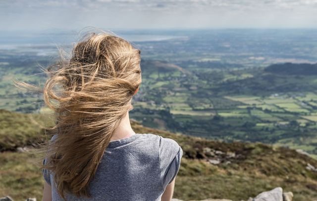 A woman enjoying spectacular views of Ireland. Have a great time traveling in Ireland with these top travel tips.