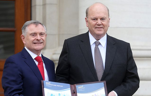 Labour Party Minister for Public Expenditure and Reform Brendan Howlin TD holds a copy of the Comprehensive Expenditure Report with Fine Gael Minister for Finance Michael Noonan TD at Government Build