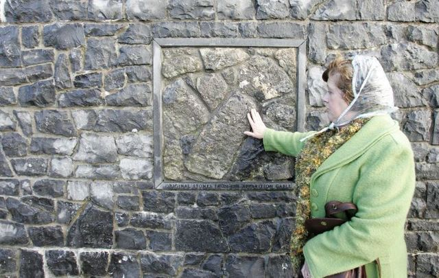 October 31, 2009: A woman touching the original stone from the apparition gable outside the shrine in Knock, Co Mayo.