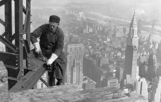 Workman on the framework of the Empire State Building, with the Chrysler Bulding in the background.