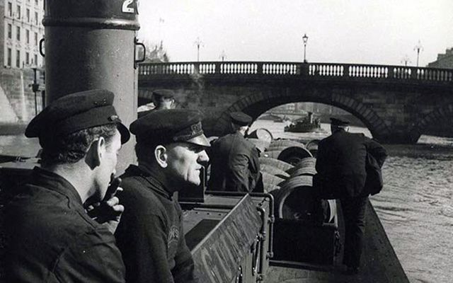 Guinness workers transport barrels of the black stuff up the River Liffey by barge.