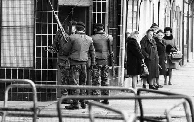 Street scene in Belfast during the Troubles. British soldiers stand next to a group of elderly ladies on a street corner.