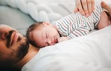 Thumb baby sleeping dads chest via getty