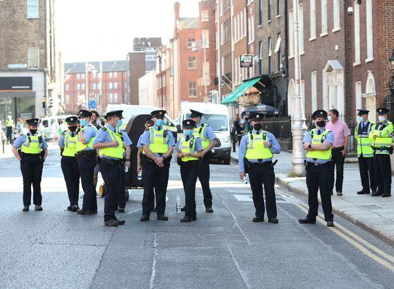 De politie houdt anti-vaccinatiepaspoortdemonstranten in Dublin in de gaten.
