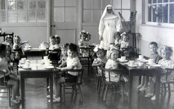 A nun and young children pose for a photo at a Mother and Baby Home.