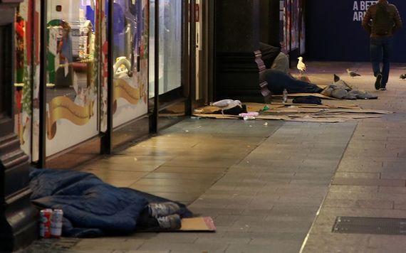 Homeless line the road, on Henry Street, Dublin 1 at night.