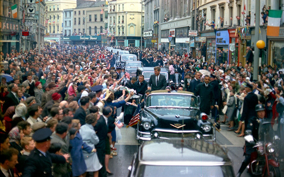 President John F. Kennedy stands in an open car while a large crowd cheers as the President's motorcade passes through Cork, Ireland. Robert Knudsen. White House Photographs. John F. Kennedy Presidential Library and Museum, Boston