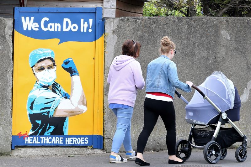 April 28, 2020: People passing a gate in Tallaght, Dublin, which artist Emmalene Blake has made into graffiti supporting of medical staff.