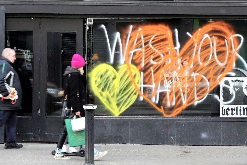 "March 16, 2020: Members of the public pass by the Berlin pub in Dublin which has a ""Wash Your Hands"" painted on the window as all pubs in Temple Bar have closed down with immediate effect."
